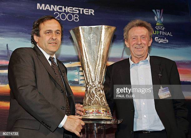 President Michel Platini and former Manchester United footballer Denis Law pose for pictures with the UEFA Cup trophy at the Manchester town hall in...