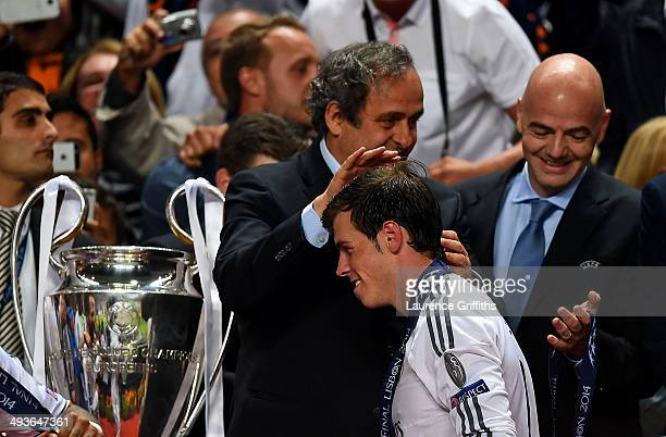 President Michel Platini congratulates Gareth Bale of Real Madrid as goes up to collect his winners medal during the UEFA Champions League Final...