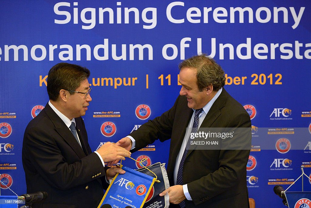 UEFA president Michel Platini (R) exchanges flags with AFC acting President Zhang Jilong (L) during a memorandum of understanding signing ceremony between the two football confederations in Bukit Jalil outside Kuala Lumpur on December 11, 2012. AFP PHOTO / Saeed Khan