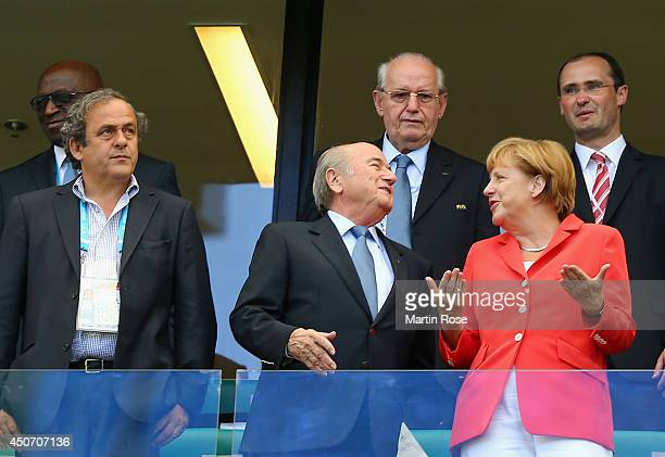 President Michel Platini FIFA President Joseph Blatter and German Chancellor Angela Merkel look on from the stands during the 2014 FIFA World Cup...