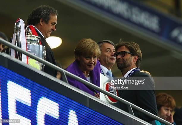 UEFA President Michel Platini German Chancellor Angela Merkel and President of the German Football Association Wolfgang Niersbach offer their...