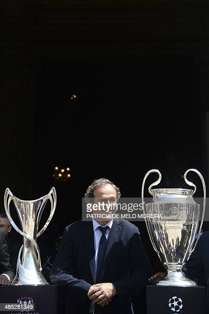 President Michel Platini poses with the UEFA Champions League trophies during a trophy handover ceremony at the Lisbon's City Hall on April 17, 2014....