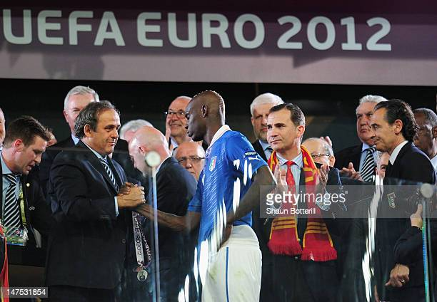 UEFA president Michel Platini shakes hands with Mario Balotelli of Italy whist Prince Felipe of Spain applauds and head coach Cesare Prandelli of...