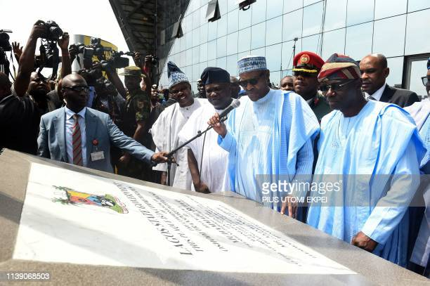 President Mohammadu Buhari flanked by Lagos State Sovernor Akinwunmi Ambode and governorelect Babajide SanwoOlu reads inscription on commemorate...
