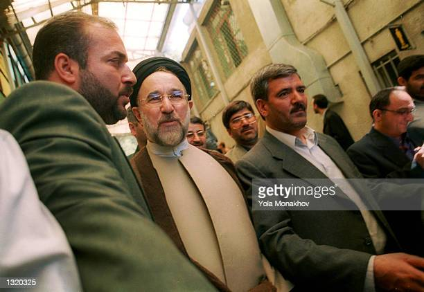 President Mohammed Khatami, center, flanked by security personnel, exits the Hosseinieh Jamaran mosque after casting his ballot in the presidential...