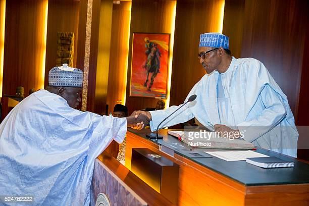 President Muhammadu Buhari congratulating INEC National Commissioner Alh Baba Shettima Arfo shortly after his swearing in Abuja 9th Nov 2015