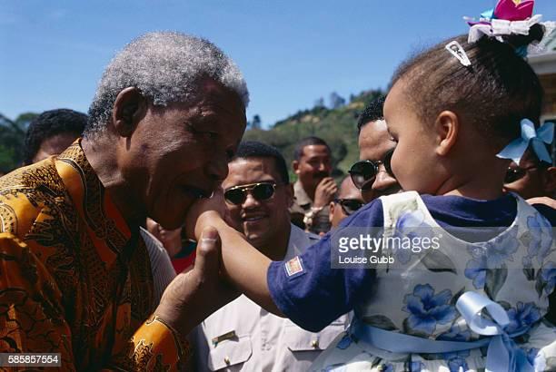 President Nelson Mandela kisses a prison worker's child when he returned to Victor Verster Prison his former residence for a visit Former President...