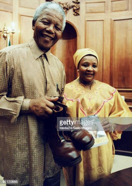 President Nelson Mandela with the pair of boots that he left 34 years ago at the house belonging to Vicky Swai in Dar es Salaam Tanzania She handed...