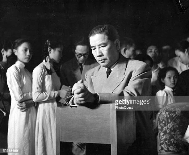 President Ngo Dinh Diem of Free Vietnam is seen kneeling during midnight Mass held on grounds of the Presidential mansion palace Saigon Vietnam circa...