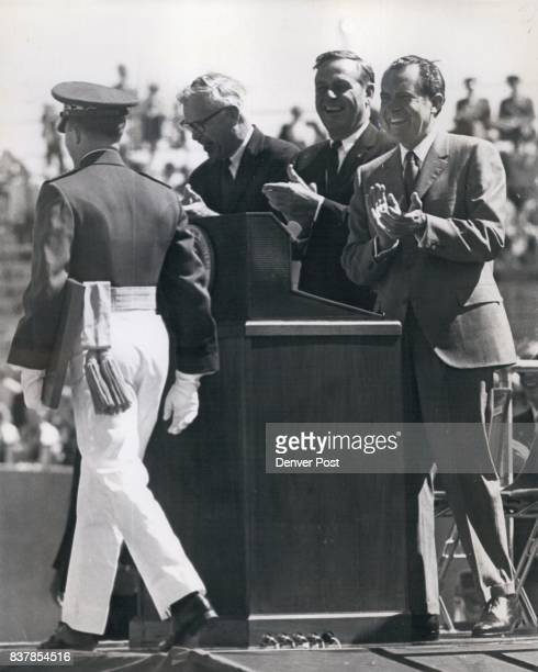 President Nixon and Gov John Love grin and applaud as Joel Allen Smith of Daytona Beach Fla walks off speaker's platform at Falcon stadium with...