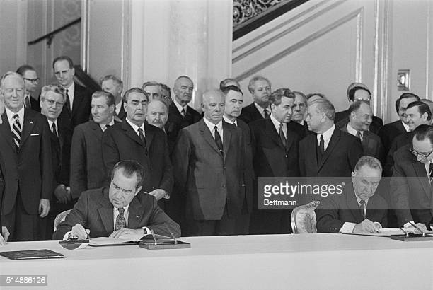 President Nixon and Soviet Premier Alexei Kosygin sign documents regarding an agreement on space flights between the two forces Leonid Brezhnev...