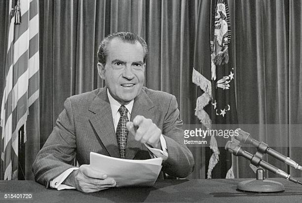 President Nixon poses in his White House office after making public a three month old US peace plan calling for simultaneous Vietnam troop...