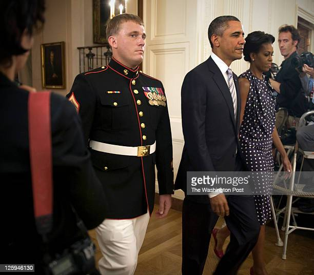 President Obama and First Lady Michelle Obama right enter the East Room with former active duty Marine Corporal Dakota Meyer left where the President...