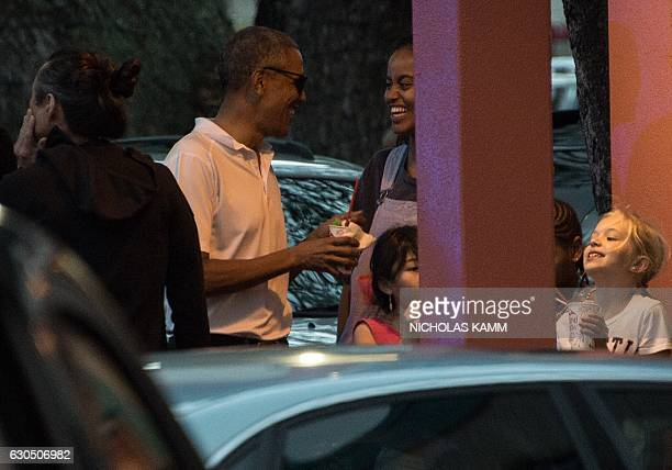 President Obama enjoys shave ice with his daughter Malia and friends at the Island Snow parlor in Kailua, Hawaii, on December 24, 2016. / AFP /...