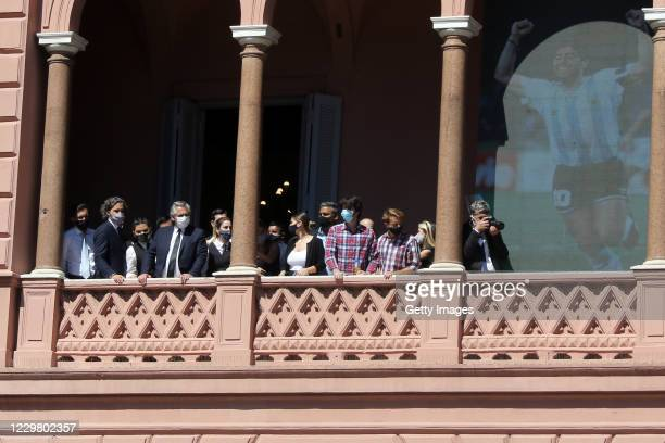 President of Argentina Alberto Fernandez watches from a balcony at Casa Rosada as riots start among fans and police officers during Diego Maradona's...