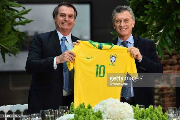 President of Argentina Mauricio Macri holds up a Brazil national soccer team jersey Number 10 presented by President of Brazil Jair Bolsonaro during...