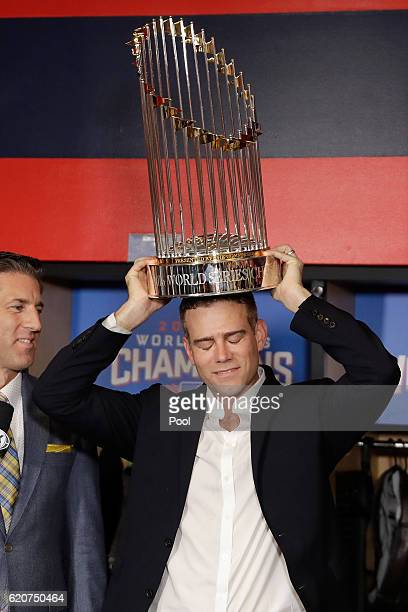 President of Baseball Operations for the Chicago Cubs Theo Epstein reacts with The Commissioner's Trophy after the Chicago Cubs defeated the...