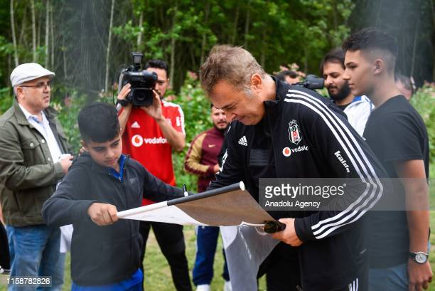 President of Besiktas, Flkret Orman signs a Besiktas flag for a fan during a training session within summer camp as part of the Turkish Super Lig new...