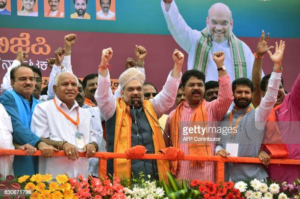 President of Bharatiya Janatha Party Amit Shah raises his hands along with senior party leaders from the state during a reception function held on...