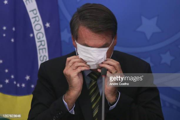 President of Brazil Jair Bolsonaro adjusts his protective mask during a press conference regarding government plans and measures about the...