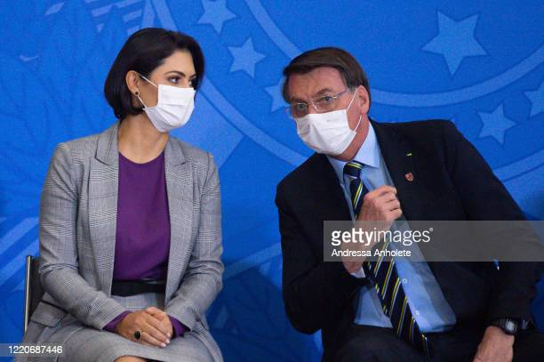 President of Brazil Jair Bolsonaro and first lady Michelle Bolsonaro talk during the ceremony for newly appointed Minister of Communications Fábio...