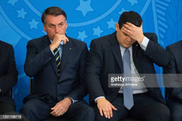 President of Brazil Jair Bolsonaro and President of the Brazilian Senate Davi Alcolumbre react during the Transmission Ceremony of the Minister of...