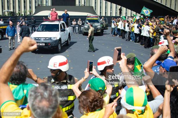 President of Brazil Jair Bolsonaro arrives before speaking to supporters in front of the Brazilian Headquarters on April 2020 in Brasilia Protesters...