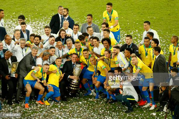 President of Brazil Jair Bolsonaro Dani Alves of Brazil and teammates pose with the trophy after winning the Copa America Brazil 2019 Final match...