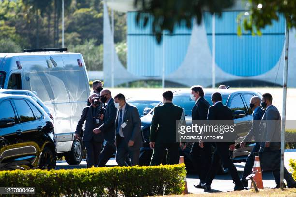 President of Brazil Jair Bolsonaro returns to his car after speaking to supporters of his government who waited for him outside the Palácio do...