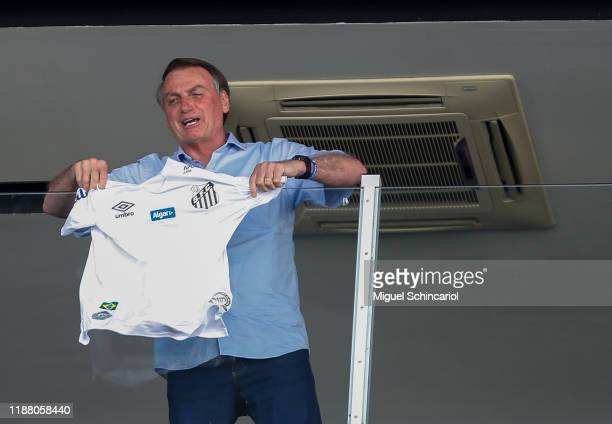 President of Brazil Jair Bolsonaro shows the jersey of Santos during a match between Santos and Sao Paulo for the Brasileirao Series A 2019 at Vila...