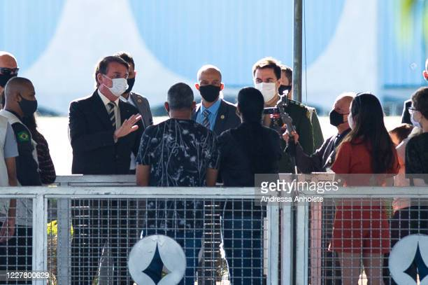 President of Brazil Jair Bolsonaro speaks to supporters of his government who waited for him outside the Palácio do Alvorada amidstthe coronavirus...