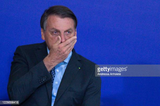 President of Brazil Jair Bolsonaro touches his face during Volunteering Alliance launch amidst the coronavirus pandemic at the Planalto Palace on...