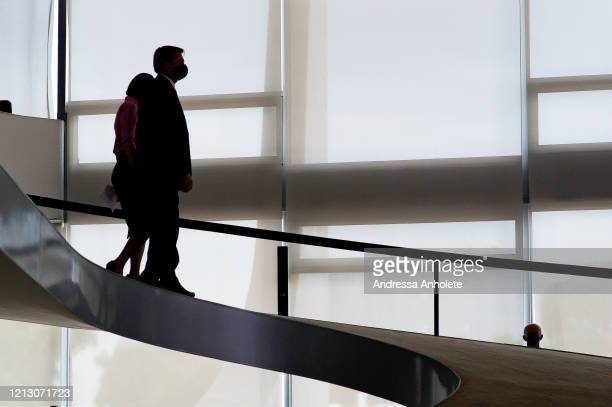 President of Brazil Jair Bolsonaro walks with his wife Michelle Bolsonaro as they arrive for the launch a new campaign against domestic...