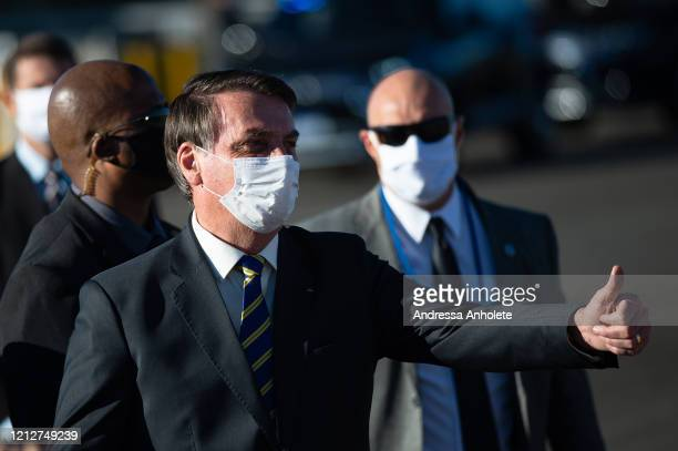 President of Brazil Jair Bolsonaro wearing a face mask speaks to supporters of his government who gathered to wait for him before flag ceremony...