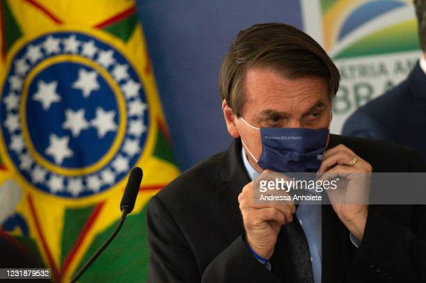 President of Brazil Jair Bolsonaro puts a face mask during the launch of Programa Aguas Brasileiras amidst the coronavirus pandemic at the Planalto...