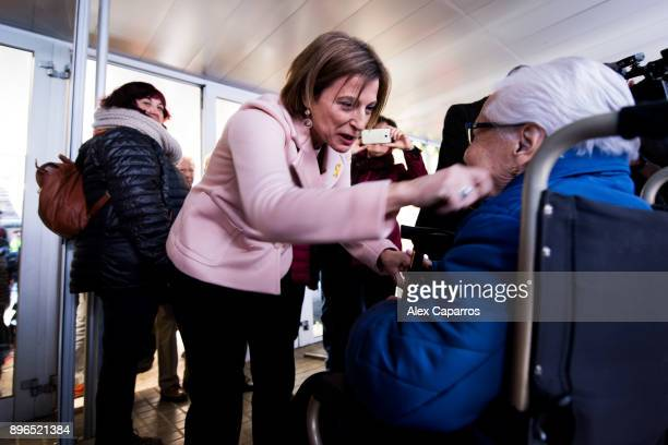 President of Catalan Parliament and 'Esquerra Republicana de Catalunya' ERC candidate Carme Forcadell speaks with a woman on a wheelchair after...
