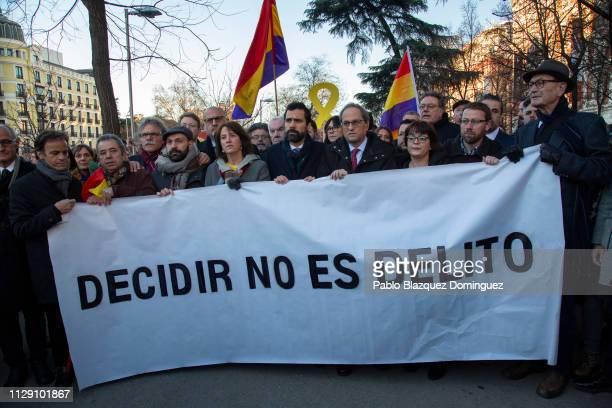 President of Catalonia Quim Torra stands with a banner reading 'To decide is not a crime' near the Supreme Court during the trial of Catalan...