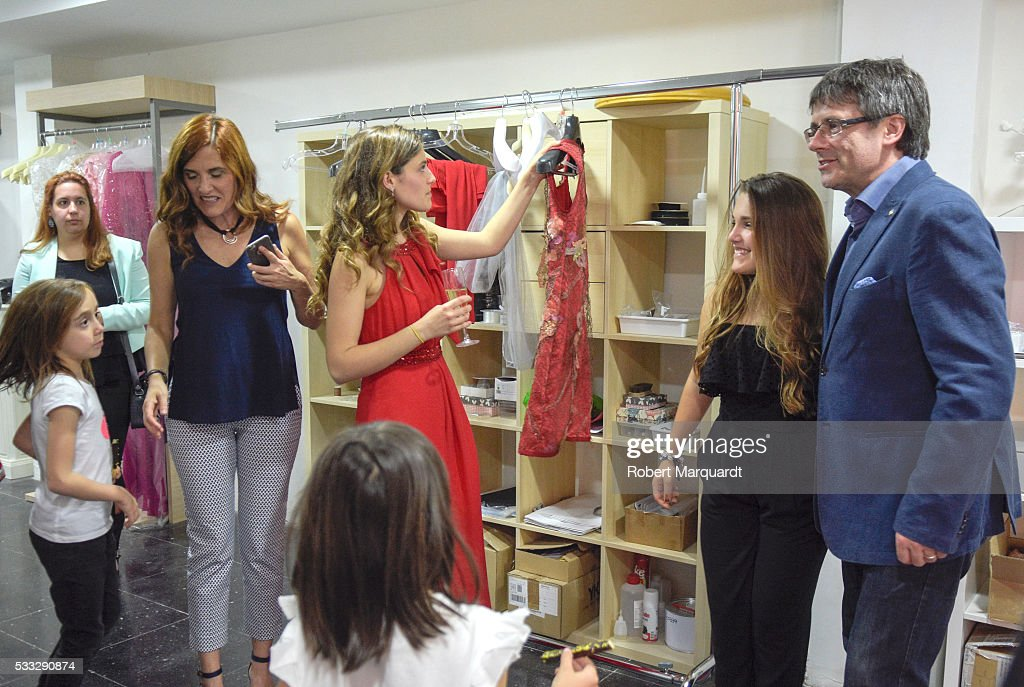 President of Catalunya Carles Puigdemont (R) and Mireia Vidal (C) attend the inauguration of the new store of Mireia Vidal Bridal on May 21, 2016 in Barcelona, Spain.