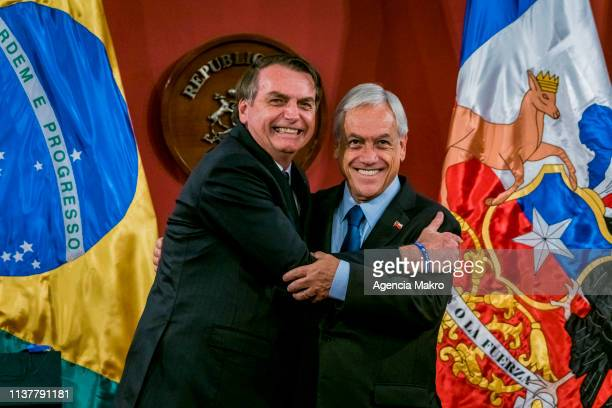 President of Chile Sebastián Piñera and Brazilian President Jair Bolsonaro embrace at the end of joint statements during the official visit of the...