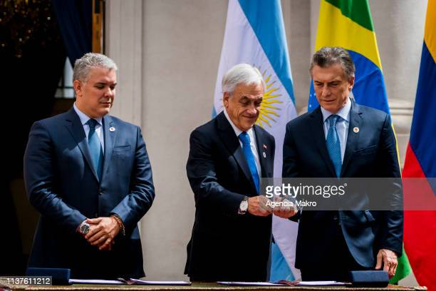 President of Chile Sebastián Piñera hands a pen to President of Argentina Mauricio Macri as he prepares to sign the agreement of Santiago after the...