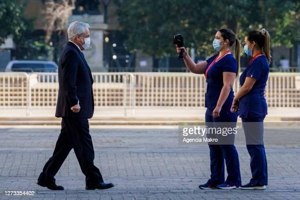 President of Chile Sebastián Piñera has his body temperature taken as he enters Palacio de La Moneda for the official family photo during the...