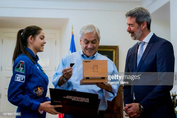 President of Chile Sebastián Piñera next to Esteban Rodriguez President of Accenture Chile receives a gift from Alyssa Carson an aspiring astronaut...