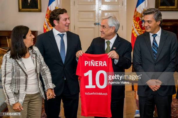 President of Chile Sebastián Piñera shows the shirt with the number ten that was delivered by the Minister of Sports Pauline Kantor next to the...