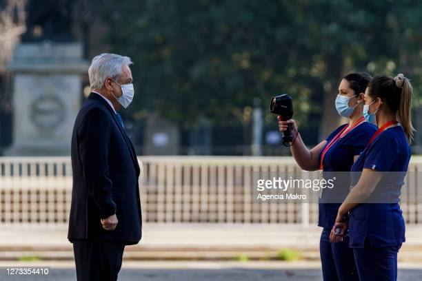 President of Chile Sebastián Piñera stands to have his body temperature taken before entering Palacio de La Moneda for official photography during...
