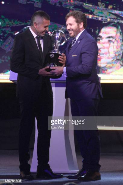 President of CONMEBOL Alejandro Dominguez gives a Copa Libertadores Trophy replica to former player and current second Vice President of Boca Juniors...