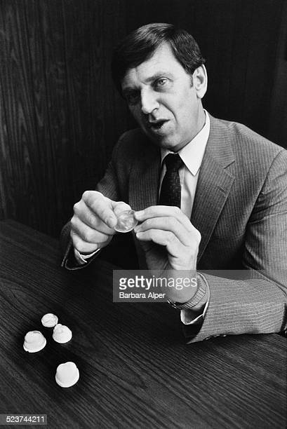 President of Contracap Paul Moriarty displays some of the company's contraceptive caps New York City USA 13th August 1982