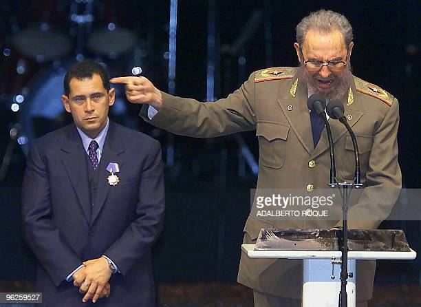 President of Cuba Fidel Castro speaks as Juan Miguel Gonzalez father of child rafter Elian Gonzalez listens after Castro presented him with the medal...