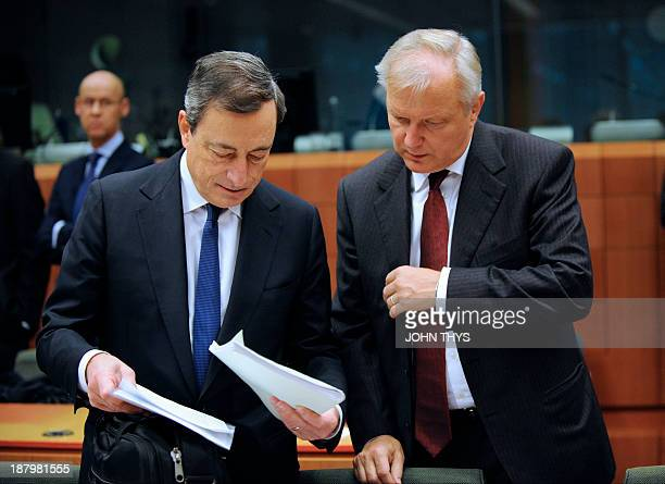 President of European Bank Mario Draghi looks at documents with EU commissioner for Economic and Monetary Affairs Olli Rehn prior to a Eurozone...