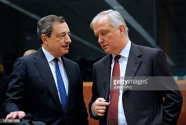 President of European Bank Mario Draghi speaks with EU commissioner for Economic and Monetary Affairs Olli Rehn prior to a Eurozone finance ministers...