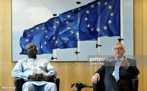 President of European Commission JeanClaude Juncker poses next to president of Liberia George Weah prior to their meeting at the EU headquarters in...